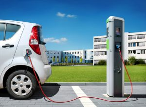 Electric,Car,On,Charging,Spot,In,Front,Of,Architecture,Office